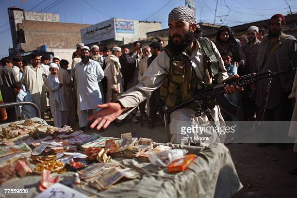 A local Taliban militant contributes at a donation table for 'mujahideen' in the village of Koza Bandi October 30 2007 in the Swat Valley of Pakistan...