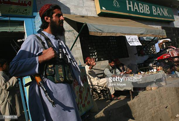 A local Taliban militant guards a table with a sign reading 'donations for mujahideen' in the Talibanheld village of Koza Bandi October 30 2007 in...