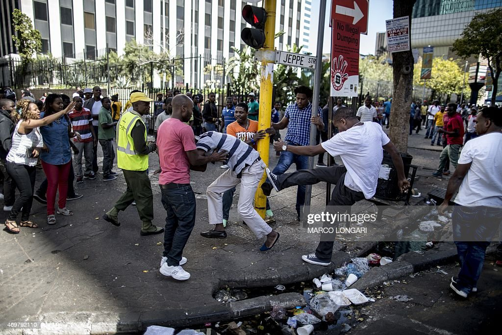 A local taxi driver is pushed around during a confrontation with foreign nationals in the Johannesburg Central Business District on April 15 2015 AFP...