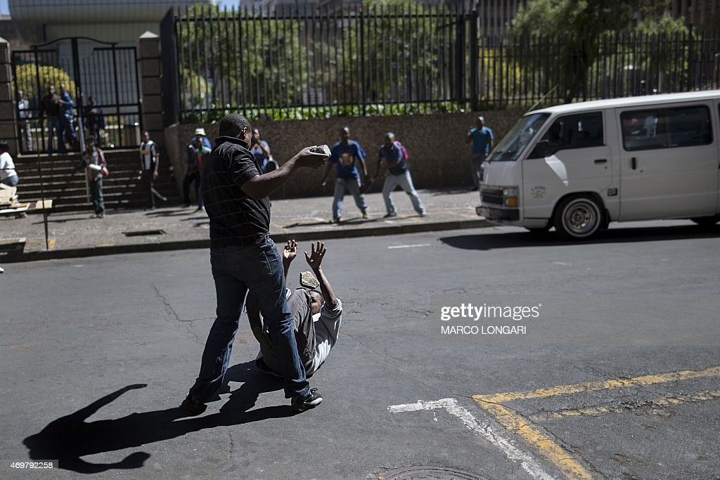 A local taxi driver pelts with stones a man on the ground during a confrontation with foreign nationals in the Johannesburg Central Business District...