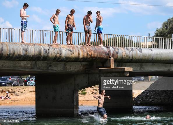 Local teenagers jumping into Narrabeen Lagoon from the road bridge on January 11 2017 in Sydney Australia High temperatures combined with rising...