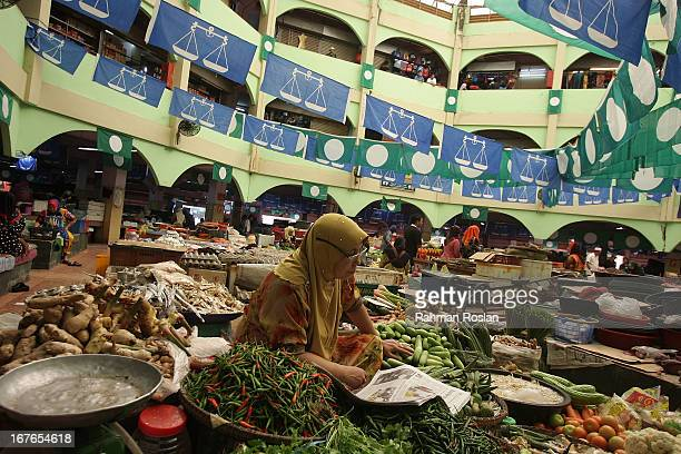 A local trader reads newspaper as she waits for customers at Pasar Besar Siti Khadijah on April 27 2013 in Kota Bharu Malaysia The election set for...