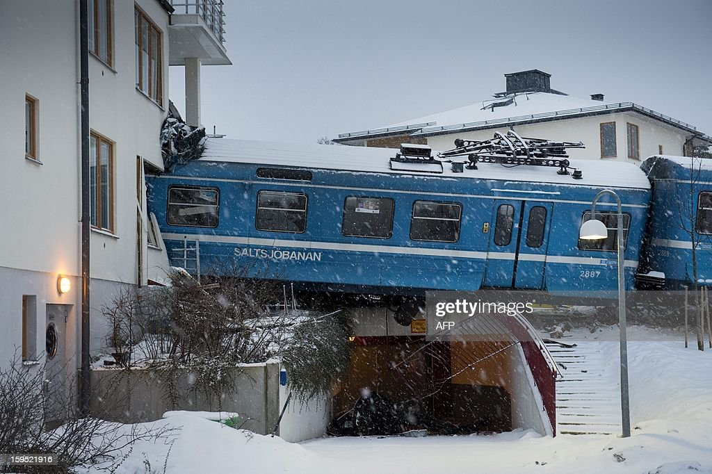 A local train derailed into a residential building in Saltsjoebaden, Sweden, on January 15, 2013.A domestic cleaner stole the train and drove it into the building and was taken to hospital after the crash. AFP PHOTO / SCANPIX SWEDEN/ JONAS EKSTROMER SWEDEN OUT