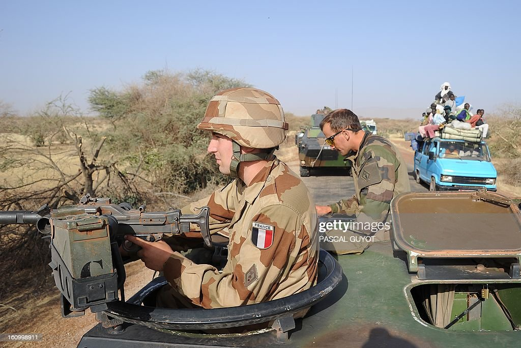 A local truck drives by a convoy of French army vehicules heading toward Gao on February 7, 2013 on the road from Gossi. Four Malian civilians were killed by a landmine in territory reclaimed from Islamist rebels, police said as France mulled handing over its four-week-old intervention to UN peacekeepers.