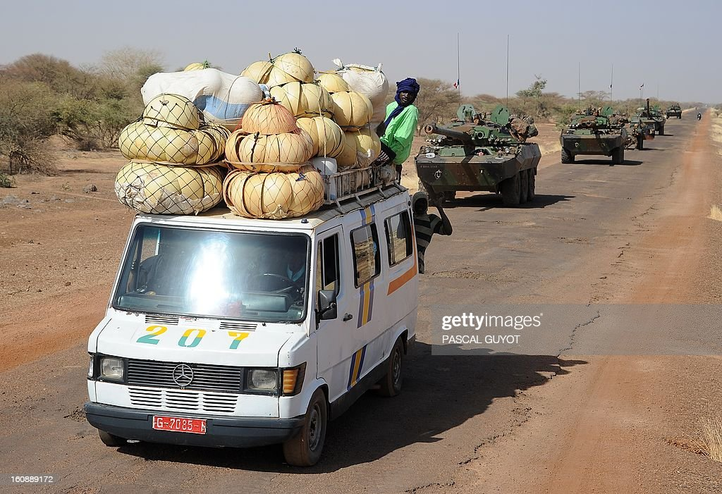 A local truck passes by a convoy of French army vehicules heading toward Gao on February 7, 2013 on the road from Gossi. Four Malian civilians were killed by a landmine in territory reclaimed from Islamist rebels, police said as France mulled handing over its four-week-old intervention to UN peacekeepers.