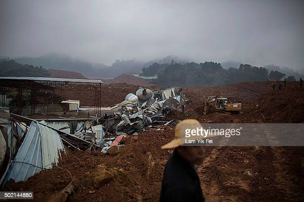 A local villager stands at the site as rescuers search a collapsed building after a landslide destroyed or damaged more than 30 buildings on December...