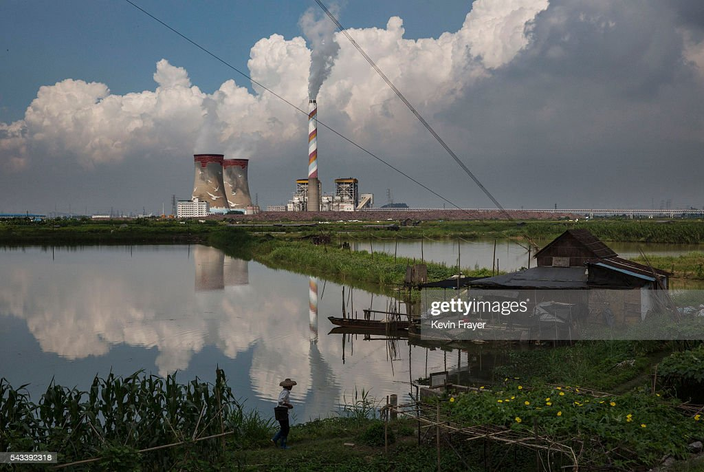A local villager walks to her house backdropped by a coal fired plant on Shazai Island where the Sun YatSen UniversityMichigan University Joint...