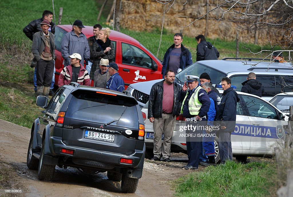 Local villagers are gathered on a crossroad in the village of Velika Ivanca, 40 kilometres south of capital Belgrade, on April 9, 2013, where a man shot dead 13 relatives and neighbours, including a two-year-old child, in the country's worst killing spree in two decades..