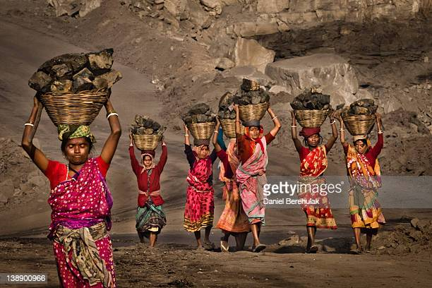 Local villagers carry coal after having scavenged the coal illegally from an opencast coal mine in the village of Jina Gora on February 11 2012 near...