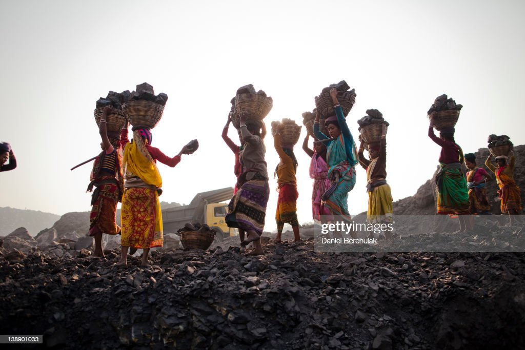Local villagers carry coal after having scavenged the coal illegally from an open-cast coal mine in the village of Jina Gora on February 11, 2012 near Jharia, India. Villagers in India's Eastern State of Jharkhand scavenge coal illegally from open-cast coal mines to earn a few dollars a day. Claiming that decades old underground burning coal seams threatened the homes of villagers, the government has recently relocated over 2300 families to towns like Belgaria. Villagers claim they were promised schools, hospitals and free utilities for two years, which they have not received. As the world's power needs have increased, so has the total global production of coal, nearly doubling over the last 20 years according to the World Coal Association.