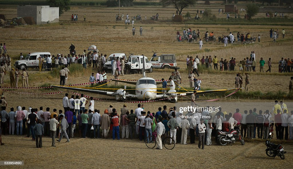 Local villagers gather around the site as security personnel secure the site where an air-ambulance crash landed at Village Kair in Nazafgarhon May 24, 2016 in New Delhi, India. An air ambulance coming from Patna with a patient, who had suffered a brain stroke, and six others on board crash landed in Najafgarh area of South West Delhi after both its engines shut down one after the other but all passengers escaped unhurt.