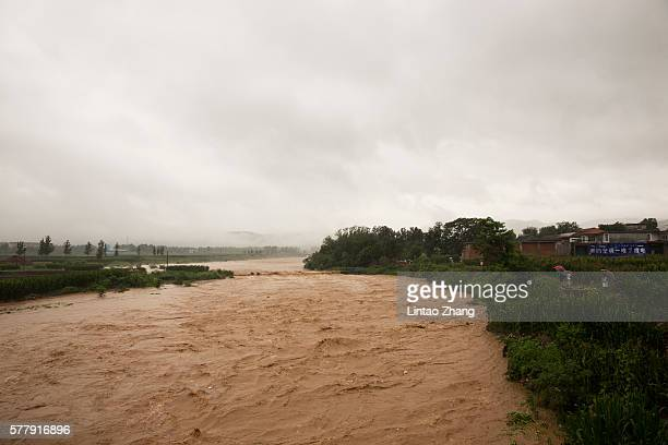 Local villagers look at flash floods on July 19 2016 at Linzhou Henan Province China Torrential rain has caused severe flooding in Northern China...