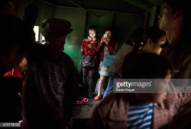 Local villagers look at their mobile phones as they and others ride in the carriage of a coal powered train on March 26 2015 near the town of Shixi...