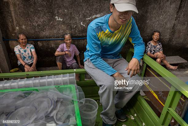 Local villagers look on as researcher Yang Gangyong waits to release adult mosquitos on Shazai Island where the Sun YatSen UniversityMichigan...