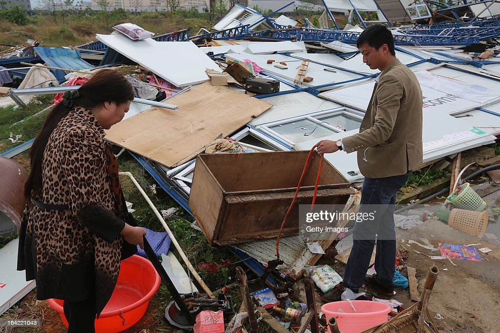 Local villagers search for their belongings among a collapsed building on March 20, 2013 in Daoxian, China. Three people have been killed and about 50 others injured after a tornado struck Central China's Hunan Province early on Wednesday morning.