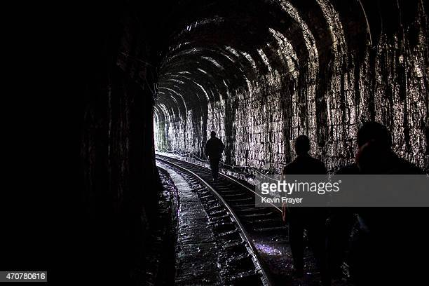 Local villagers walk through a tunnel to catch a coal powered steam train on March 29 2015 near the village of Bagou Sichuan Province in Southern...