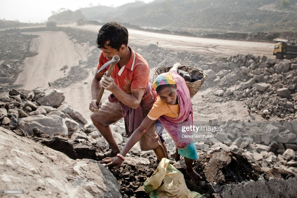 Local villagers work to scavenge coal illegally from an open-cast coal mine in the village of Jina Gora on February 11, 2012 near Jharia, India. Villagers in India's Eastern State of Jharkhand scavenge coal illegally from open-cast coal mines to earn a few dollars a day. Claiming that decades old underground burning coal seams threatened the homes of villagers, the government has recently relocated over 2300 families to towns like Belgaria. Villagers claim they were promised schools, hospitals and free utilities for two years, which they have not received. As the world's power needs have increased, so has the total global production of coal, nearly doubling over the last 20 years according to the World Coal Association.