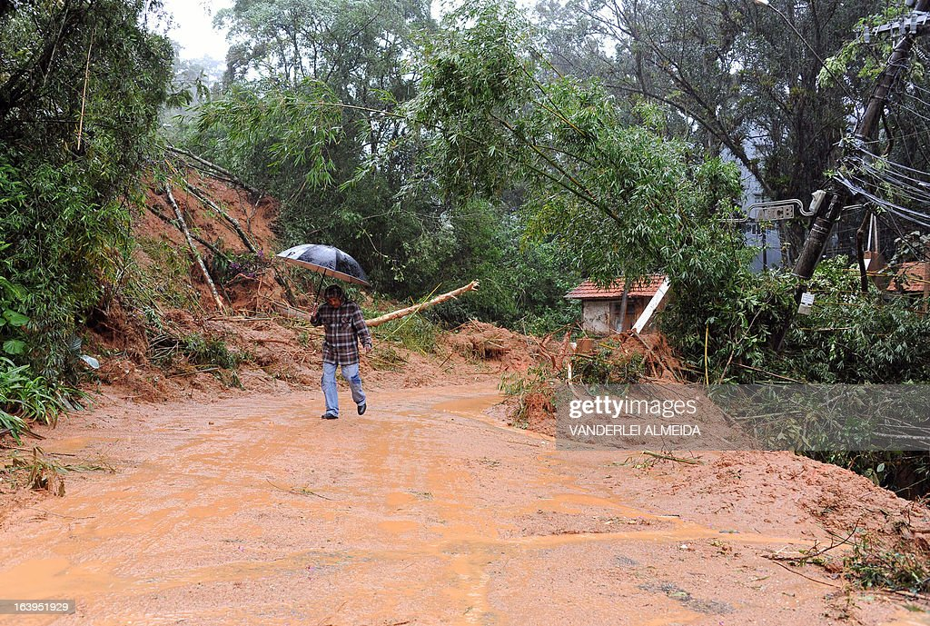 A local walks in a flooded street following landslides caused by heavy rains hitting the area, at a poor neighbourhood in Petropolis, 68 km north of Rio de Janeiro, on March 18, 2013. Floodings and mudslides triggered by heavy rains have already left 13 people dead over the past 24 hours in the Brazilian tourist town of Petropolis, whose historic center is under water.
