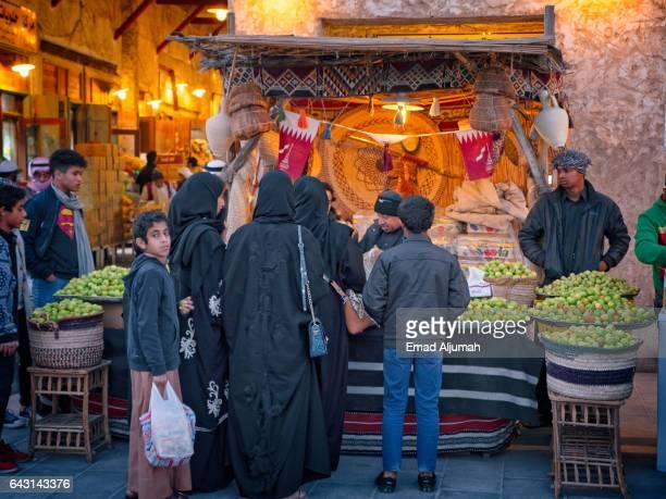 Local woman buying fruits at Souq Waqif, Doha, Qatar - February 3, 2017
