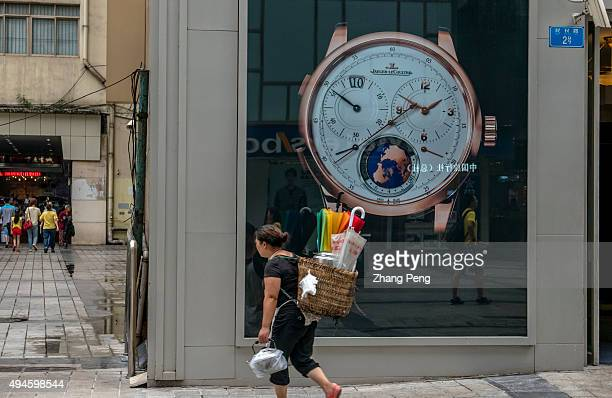 A local woman carries a bamboo basket walking past a luxury watch shop at Jiefangbei CBD With a growth rate of 11 percent the municipality of...
