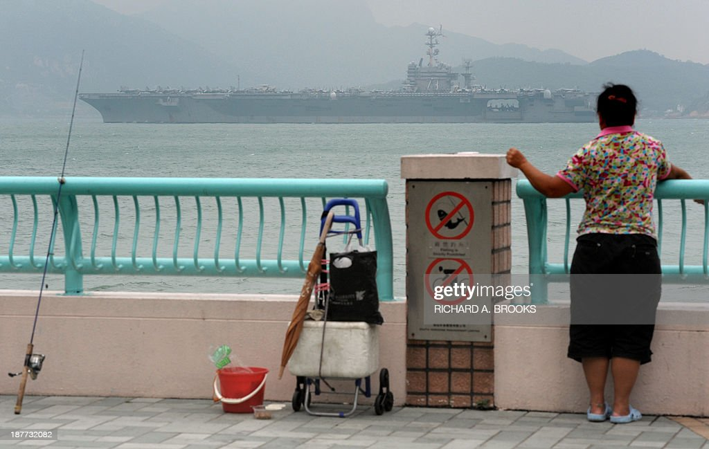 A local woman fishes off a promenade as the aircraft carrier USS George Washington sails out of Hong Kong on November 12, 2013 to join the rescue and relief operations in the Philippines following Super Typhoon Haiyan. US and British warships were deployed on November 12 to the typhoon-ravaged Philippines where well over 10,000 people are feared dead and countless survivors are begging for help in rain-soaked wastelands. Four days after Super Typhoon Haiyan destroyed entire coastal towns in mostly poor central islands with record winds and tsunami-like waves, the magnitude of the disaster continued to build with almost unimaginable horror.
