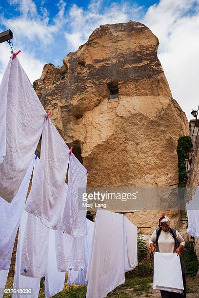 Local woman folding the drying linen outdoors in Goreme village Cappadocia Turkey