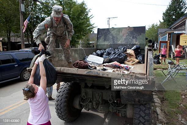 A local woman hands a bag of debris to an Army National Guardsman from the 131st Engineer Company in Westminster Vermont on West Main Street where...