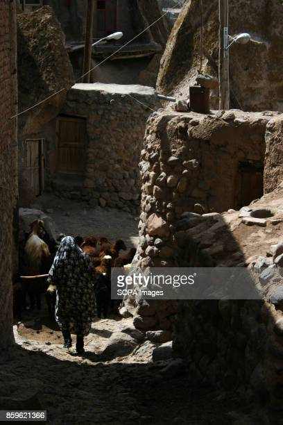 A local woman is pictured as she walks through the narrow alley inside the village The tiny village of Kandovan in the Iranian East Azerbaijan...