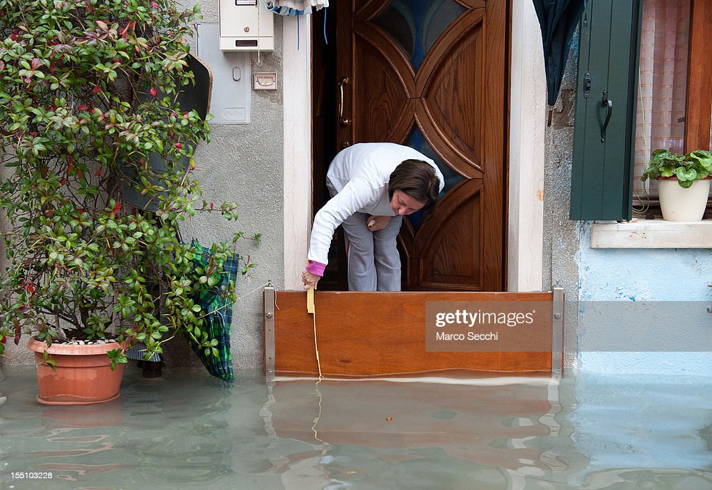 A local woman measures the rising water level in Burano on November 1, 2012 in Venice, Italy. More than 59% of Venice has been been left flooded, after the historic town was hit by exceptionally high tides. The sea level rose above 140cm overnight was expected to remain above critical levels for about 15 hours.