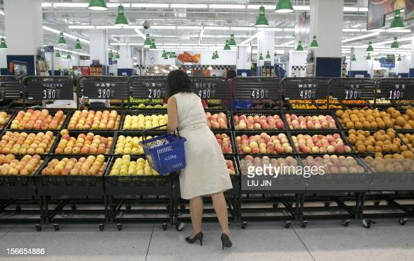 A local woman picks up the fruits imported from the US at the newopened Walmart supermarket in Chengdu in China's southwestern province of Sichuan 26...