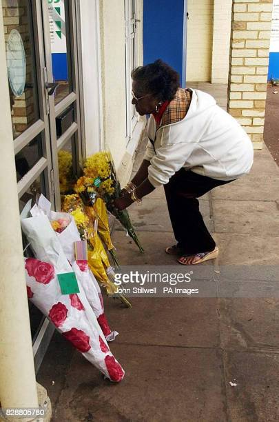 A local woman places flowers at the front door of the Physical Limit Gym and fitness centre in the town centre of Hoddesdon Hertfordshire following...