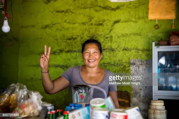 A local woman shows off her restaurant or 'warung' on Serangan Beach, Bali.