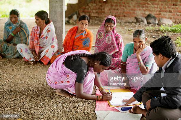 A local woman signs a register to receive a loan during a meeting organized by SKS Microfinance Ltd in Sadasivpet India on Friday Aug 6 2010 SKS...