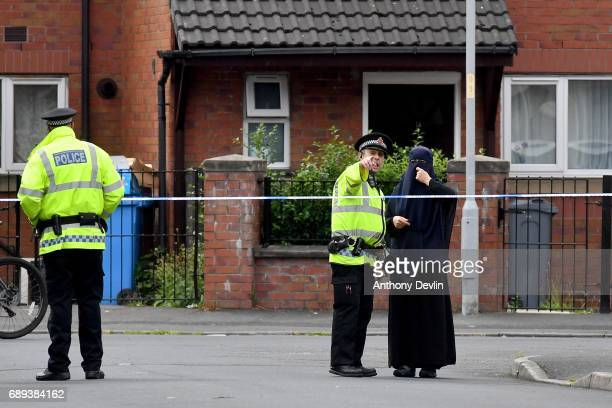 A local woman speaks to a Police offficers as police close the road leading to Quantock Street in the Moss Side area of Manchester where a raid was...