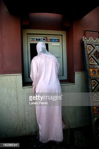 Local woman using ATM, Delemma el-Fna. : Foto de stock
