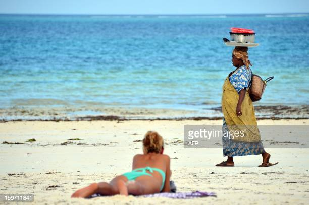 A local woman walks on a beach past a tourist on January 7 2013 in Zanzibar AFP PHOTO / GABRIEL BOUYS