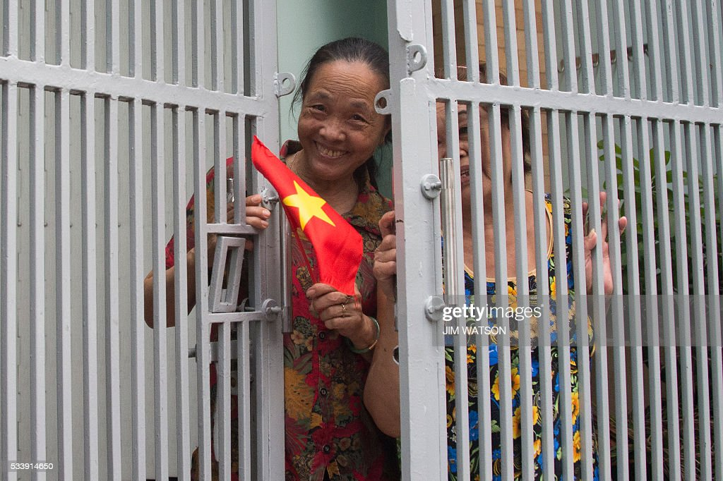 A local woman waves a flag out the door as US President Barack Obama's motorcade passes in Ho Chi Minh City on May 24, 2016. US President Barack Obama told communist Vietnam on May 24 that basic human rights would not jeopardise its stability, in an impassioned appeal for the one-party state to abandon authoritarianism. / AFP / JIM