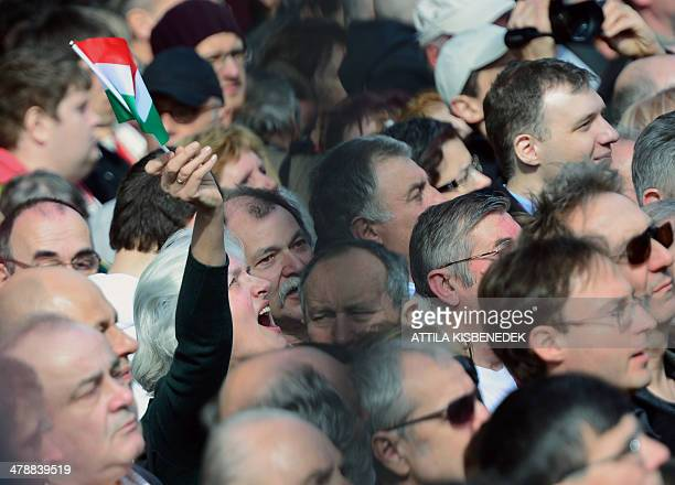 A local woman waves with her small national flag as the Hungarian Prime Minister delivers a speech in front of the National Museum of Budapest on...