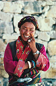 Local woman, wearing traditional Tibetan dress, outside her home in Tingri.