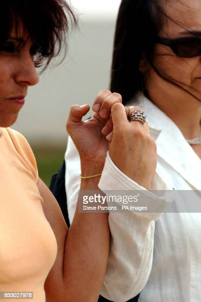 A local woman wears a yellow string band on her wrist as a symbol of hope as she joins others outside a church in Praia Da Luz Portugal for a minute...