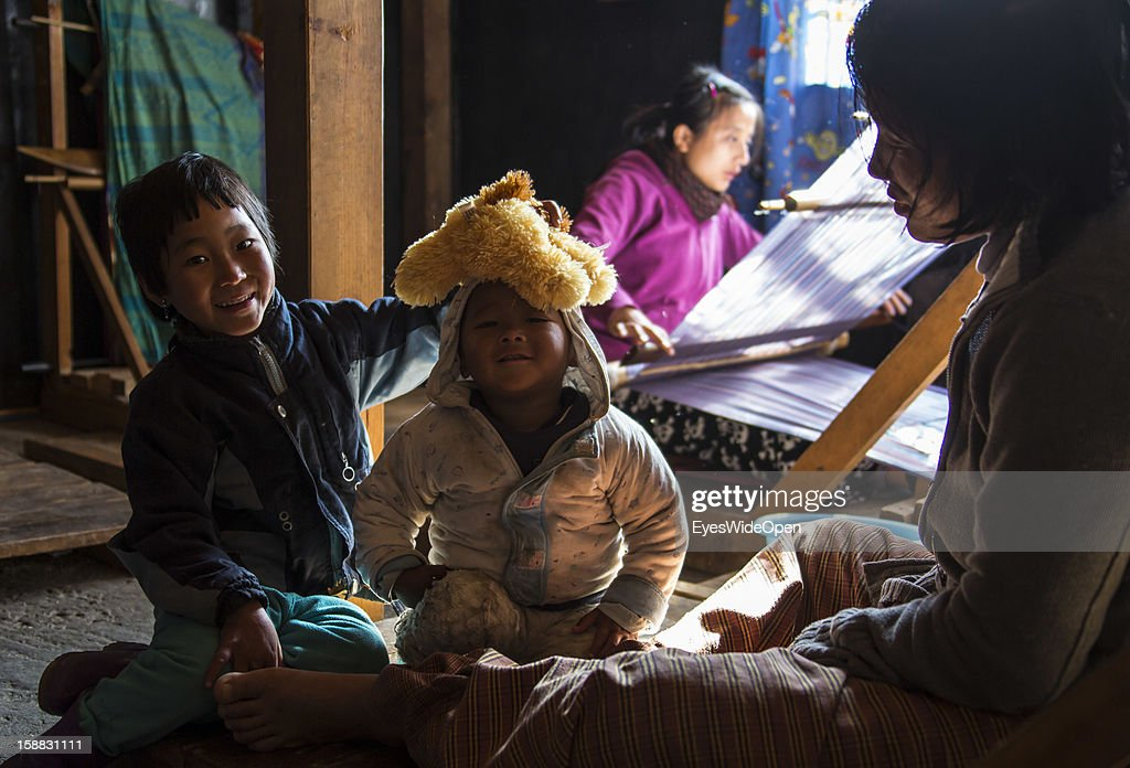 Local women show their business, craft, produce blankets and clothes on a loom while their children play around on November 18, 2012 in Thimphu, Bhutan.