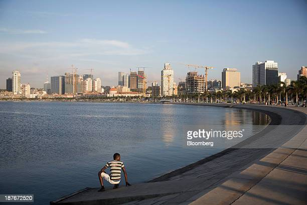 A local youth sits on the shoreline looking out towards the Bay of Luanda in Luanda Angola on Friday Nov 8 2013 Angola the largest crude oil producer...