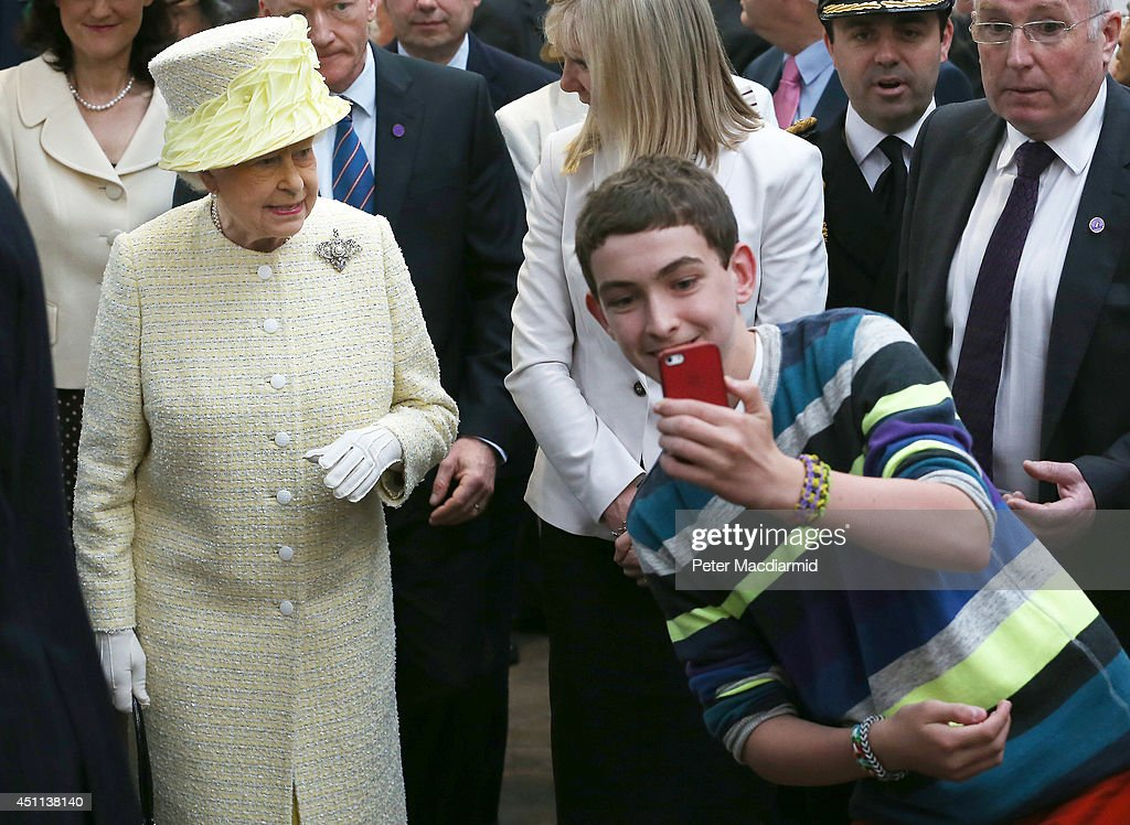 A local youth takes a selfie photograph in front of Queen Elizabeth II during a visit to St George's indoor market on June 24, 2014 in Belfast, Northern Ireland. The Royal party are visiting Northern Ireland for three days.