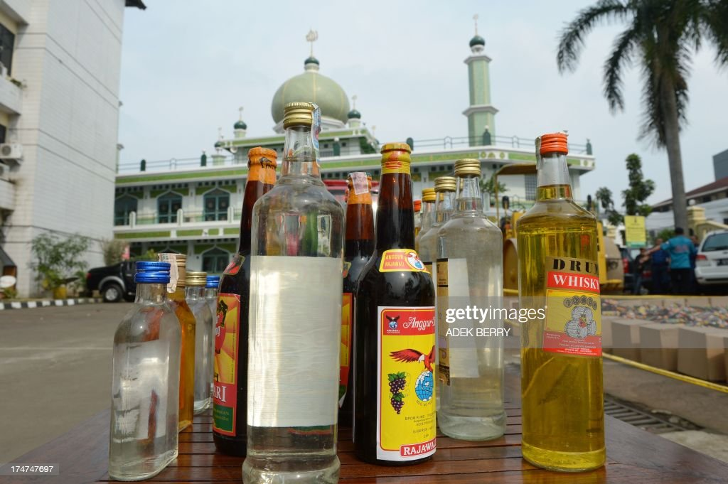 Locally made alcoholic drinks are displayed during a bottle crushing event as part of a police operation during ramadan at South Jakarta police headquarters in Jakarta on July 29, 2013. About 10,681 alcohol drinks, mostly local made were destroyed by police after they were seized from vendors who failed to show documents permitting their sale.