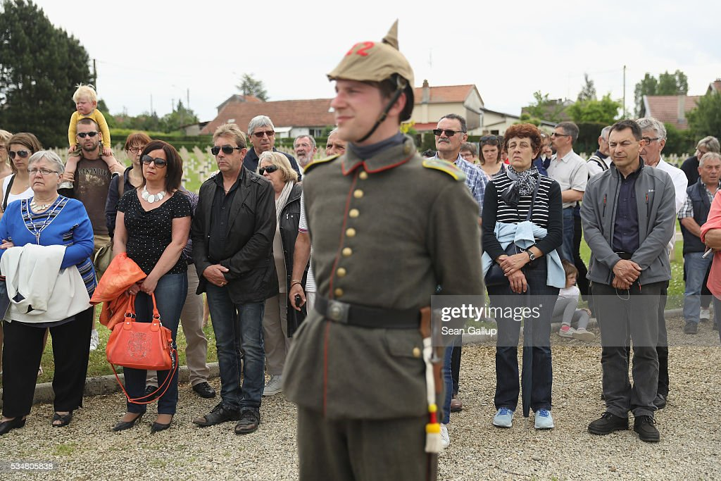 Locals and a history reenactor dressed as a World War I German soldier attend a commemoration ceremony at the World War I French cemetery, where nearly 5,000 fallen soldiers lie, on May 28, 2016 in Verdun, France. The governments of France and Germany will commemorate the 100th anniversary of the World War I Battle of Verdun with ceremonies tomorrow. Approximately 300,000 soldiers lost their lives in the 10-month campaign that was among the most grueling battles of World War I.