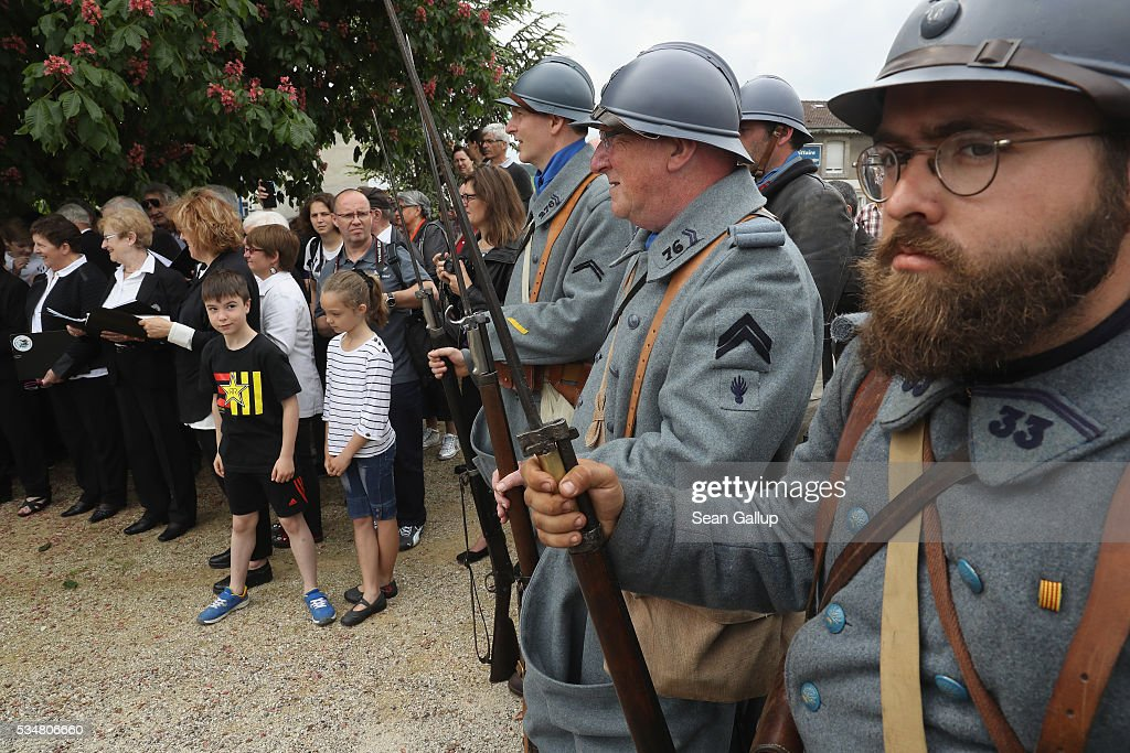 Locals and history reenactors dressed as World War I French soldiers attend a commemoration ceremony at a World War I memorial in Haudainville village on May 28, 2016 near Verdun, France. The governments of France and Germany will commemorate the 100th anniversary of the World War I Battle of Verdun with ceremonies tomorrow. Approximately 300,000 soldiers lost their lives in the 10-month campaign that was among the most grueling battles of World War I.