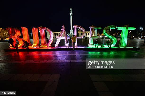 Locals and tourists pose for photos in front of a giant illuminated 'Budapest' sign at the Heroes square of Budapest on March 23 2014 This new...