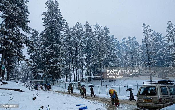 Locals and tourists wait for vehicles to reach Gulmarg during a fresh snowfall on January 04 2016 in Tangmarg 40 Km to the west of Srinagar the...