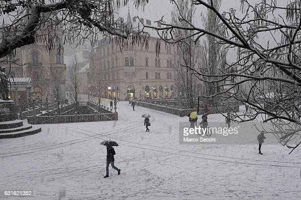 Locals and tourists walk on Tromostovje on January 13 2017 in Ljubljana Slovenia Most of Slovenia was covered by heavy snowfalls for the first time...