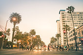 Locals and tourists walking on zebra crossing in Ocean Ave in Santa Monica after sunset - Crowded streets of Los Angeles and California state - People are slightlu blurred to make them unrecognizable